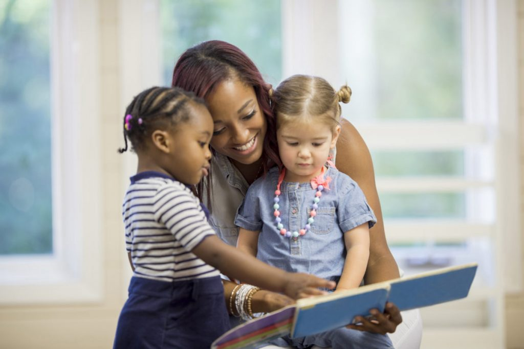 female advocate reading with two little girls